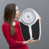 Smart looking 20s girl in love with her weighting scale Royalty Free Stock Images