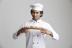 Smart male chef holding cookies. A male chef enjoying fragrance of cookies on grey gradient background stock images