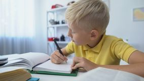 Smart male child doing homework, writing in notebook, education and knowledge stock footage