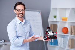 Smart male scientist in glasses presenting a little robot Royalty Free Stock Images