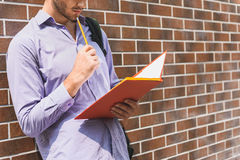 Smart male student learning subject. Pensive young man is reading papers with concentration. He is standing and leaning on wall Stock Image