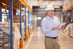 Smart male worker checking the warehouse. Safety control. Smart warehouse worker holding a tablet while checking the warehouse safety Stock Images