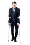 Smart man with crutches trying to walk Royalty Free Stock Photos