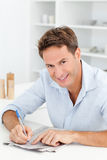 Smart man doing a cryptic crossword Royalty Free Stock Photo