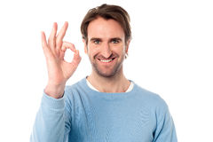 Smart man showing okay sign. Handsome young man showing OK sign over white Royalty Free Stock Photo