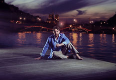 Smart man sitting close to the river Stock Photos