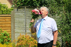 Smart man smelling a bunch of flowers. Royalty Free Stock Photography