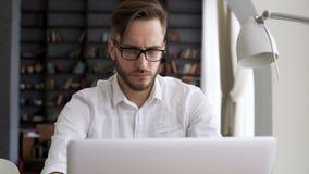 Smart man som arbetar vid datoren i workspace stock video