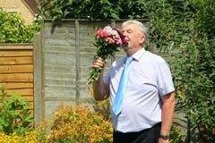 Smart man som luktar en grupp av blommor Royaltyfri Fotografi