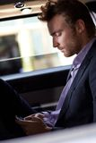 Smart man som smsar på mobiltelefonen i elegant bil Royaltyfri Foto