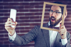 Smart man taking selfie while holding frame Stock Photo