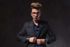 Smart man wearing glasses while looking at the camera in dark st. Portrait of fashionable smart man wearing glasses while looking at the camera in dark studio Stock Photos