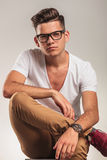 Smart man wearing glasses sitting on a chair with legs crossed Stock Photos