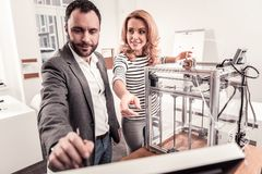 Smart man and woman discussing 3D printing. Business communication. Smart pleasant men and women discussing 3D printing standing at the modern office royalty free stock image