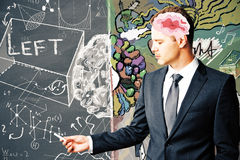 Smart man writing on brick wall. Side view of young businessman with abstract brain writing with chalk stick on background with scientific formulas. Knowledge stock photo