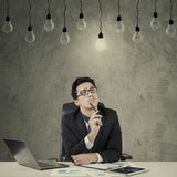 Smart manager looking at illuminated lamp Stock Photo