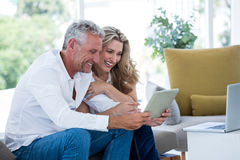 Smart mature couple using digital tablet Stock Images