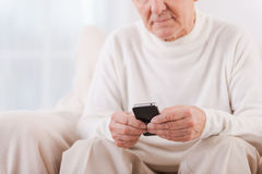 Smart maturity. Close-up of senior man holding mobile phone while sitting in chair royalty free stock image
