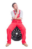 Smart mechanic thinking and sitting on tire Royalty Free Stock Image
