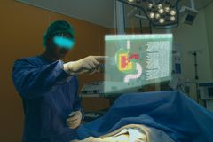 Smart medical technology concept, doctor use glasses to use augmented reality to show the injury of stomach of the patient for ana. Lysis and find the way to stock photography