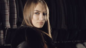 Smart model stands in pose in fur coat in fashionable rich boutique stock footage