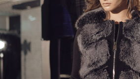 Smart model stands in pose in the rich fur coats for advertising. Slowly