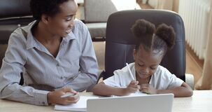 Smart mom with cute little daughter doing homework remotely, older sister helps preschool girl with assignment teaches