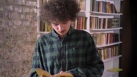 Smart nerdy student med läseboken för lockigt hår i arkiv och anseendet, bokhyllor i bakgrund lager videofilmer