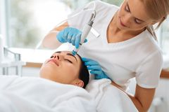 Smart nice cosmetologist looking at the clients face. Professional facial treatment. Smart nice cosmetologist looking at the clients face while doing hydrafacial royalty free stock photos