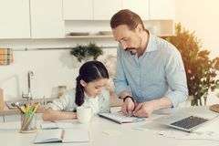 Smart nice man helping his daughter with homework. Maths homework. Smart handsome serious men holding pair of compasses and doing the measurement while helping Stock Image