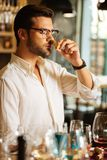 Smart nice man holding a wine bottle cork. Elite alcohol. Smart nice man holding a wine bottle cork while checking its smell stock photo