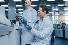 Smart nice man sitting on the chair. Scientific research. Smart handsome nice men sitting on the chair in the lab and holding a test tube while carrying out a Stock Photo