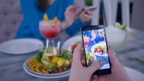 Smart - o telefone na mão da mulher do blogger faz a foto o vegetariano saudável que come durante o almoço para redes sociais, fi video estoque
