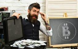 Smart och rikt Affärsman i serverrum Skäggig man med kassapengar Uppsökt hipster med bitcoinsymbol och arkivfoton