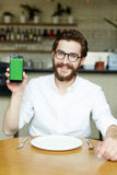 Smart order. Happy cafe visitor showing online menu in smartphone Stock Photography