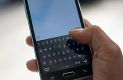 Smart phon and hand  touch on keypad. Person touch text on keypad Royalty Free Stock Images