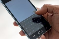 Smart phon and hand  touch on keypad. Person touch text on keypad Royalty Free Stock Image