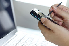 Smart phone. A woman using a smart phone with a stylus and laptop at the side Royalty Free Stock Photo