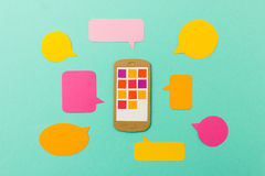 Smart phone with app icons and colorful speechbubbles Stock Photography