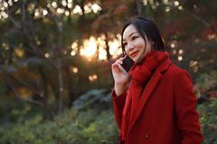 Smart phone Autumn woman talking on mobile in fall. Smart phone Autumn woman talking on mobile phone in fall. Autumn girl having smartphone conversation in sun Royalty Free Stock Image