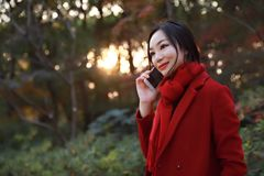 Smart phone Autumn woman talking on mobile in fall. Smart phone Autumn woman talking on mobile phone in fall. Autumn girl having smartphone conversation in sun Royalty Free Stock Photo