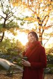 Smart phone Autumn woman talking on mobile in fall. Smart phone Autumn woman talking on mobile phone in fall. Autumn girl having smartphone conversation in sun Stock Images
