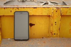 Smart phone on background of yellow steel. Royalty Free Stock Image