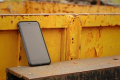 Smart phone on background of yellow steel. Royalty Free Stock Photography