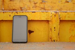 Smart phone on background of yellow steel. Stock Images