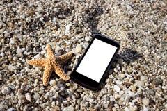 Smart phone on beach close up Stock Photos