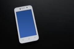 Smart Phone bianco con lo schermo blu sulla Tabella nera Immagini Stock Libere da Diritti