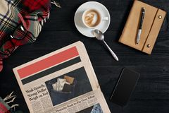 Smart phone with black display on wooden background. Newspaper and coffee on wooden table. Top view. stock photography