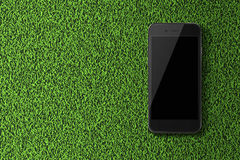 Smart phone with black screen on green grass background. Royalty Free Stock Photography
