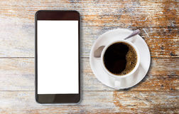 Smart phone with blank screen area and coffee cup. On vintage wooden background Stock Image